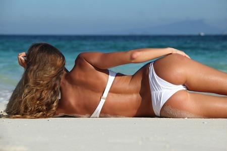 局所のビーチで横になっている bikni のセクシーな女性の後姿