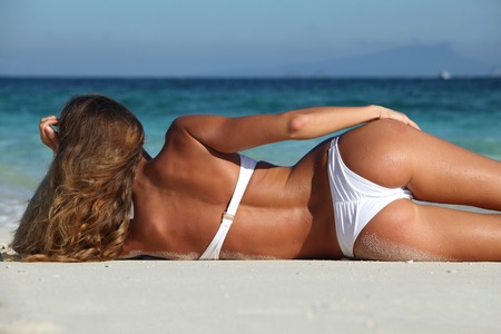 laying on back: Rear view of sexy woman in bikni lying on topical beach