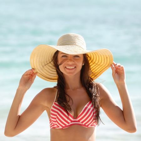 sunhat: Portrait of a beautiful young woman in sunhat on beach
