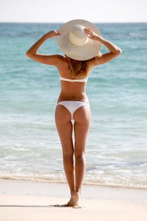 sunhat: Beautiful young woman in sunhat on beach