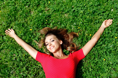 woman laying: beautiful young woman in red dress lying on grass