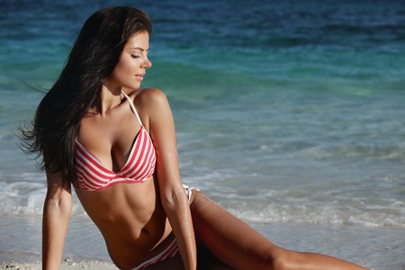 Beautiful young woman in bikini sitting on beach near sea