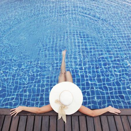Vrouw in hoed ontspannen bij het zwembad Stockfoto - 52814767