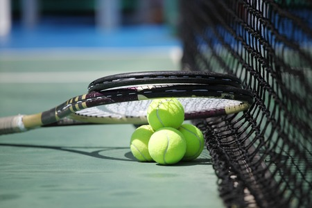Tennis balls and racket on court close up