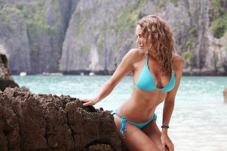 Schöne Frau im Bikini posiert auf Thai Strand sitzen auf den Felsen