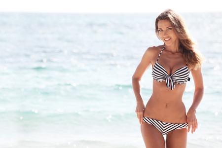 Happy woman in bikini posing on beach in Thailand 版權商用圖片