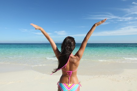 raised hands: Happy woman with raised hands on beach