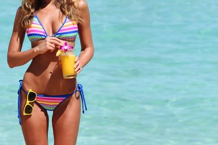 Mooie vrouw in bikini met een cocktail op het strand Stockfoto