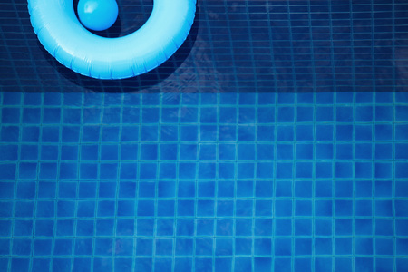 Swim ring and toy ball floating in a blue swimming pool
