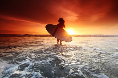 Mooie surfer vrouw op het strand bij zonsondergang Stockfoto