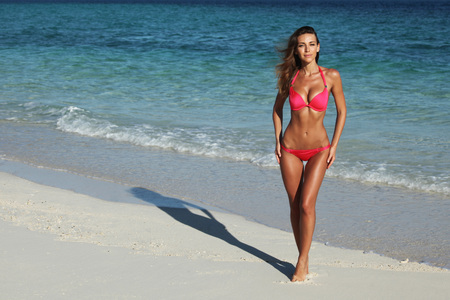 Beautiful woman in red bikni on tropical beach