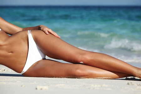 Woman with perfect body in bikini lying on beach over blue sea background
