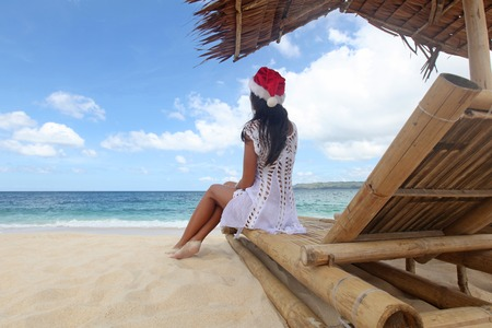 chaise lounge: Woman in Santa Claus hat sitting at chaise lounge with straw parasol on white sandy beach at Philippines
