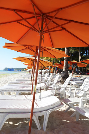 chaise lounge: Row of beach umbrellas and chaise lounge in a beach resort
