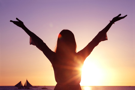 raised hands: Woman with raised hands at sunset by the sea Stock Photo