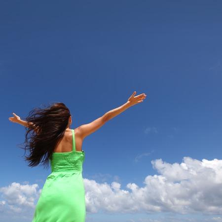 manos levantadas al cielo: Mujer con las manos levantadas sobre fondo de cielo azul
