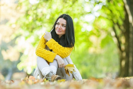 sitting on the ground: Happy woman sitting on dry leaves in autumn park at sunny day