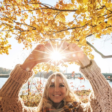 Happy woman playing with sun in autumn park photo