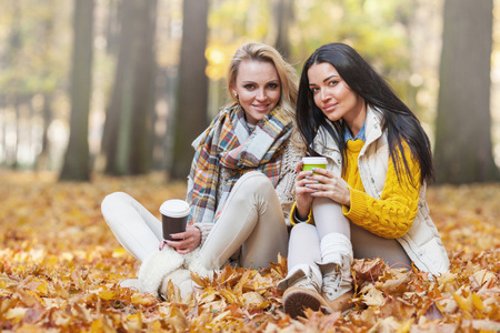 Two cheerful female friends drinking coffee in autumn park photo