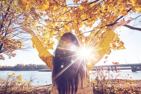 manos levantadas: Mujer feliz con las manos levantadas en el parque soleado de otoño