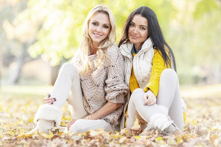 Two cheerful women sitting on dry leaves in autumn park at sunny day photo