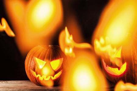 Funny glowing Halloween pumpkins on a black background Stock Photo