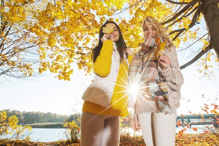 Two cheerful women in autumn park at sunny day photo