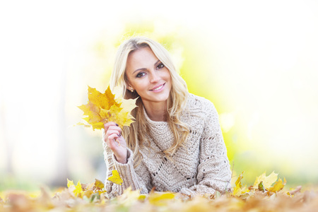 Happy woman lies on dry leaves in autumn park at sunny day photo