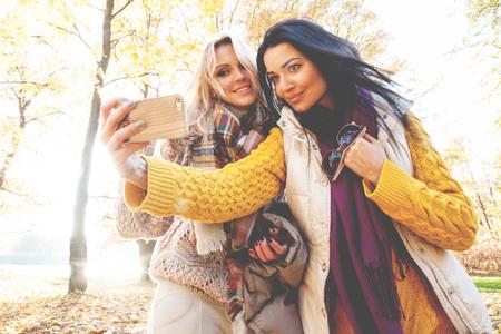 Two happy women taking selfie in autumn park photo