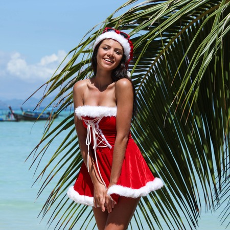 mrs  claus: Beautiful woman in Mrs. Claus custume on tropical beach with palms, Christmas vacations concept Stock Photo