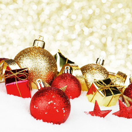 gold christmas decorations: Christmas card with colorful decorations in snow on gold background Stock Photo