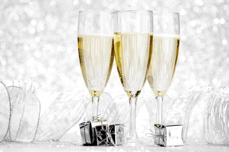 birthday decoration: Glasses of champagne and silver gifts on glitter background