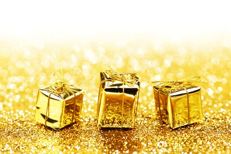 shiny: Decorative golden boxes with holiday gifts on shiny glitter background Stock Photo