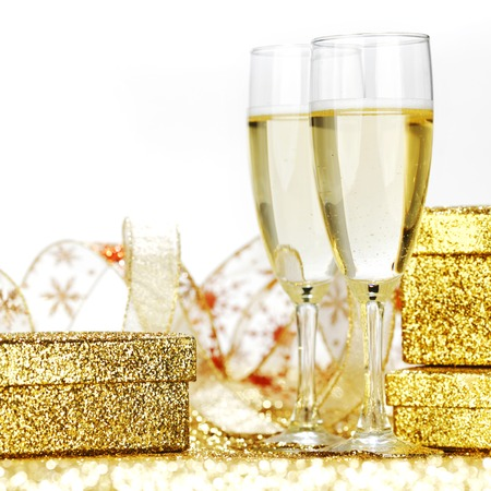 champagne glasses: Champagne in glasses and gift box on golden background with twinkle lights Stock Photo