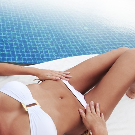 tanned body: Beautiful woman with fit, tanned body in bikini sitting and tanning poolside