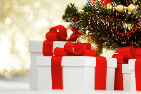Studio shot of white gifts with red ribbons under Christmas tree, on bokeh background
