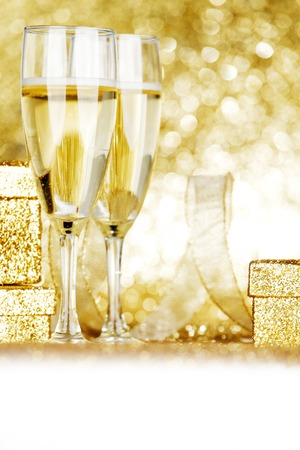champagne glasses: Glasses of champagne and present on golden glitter background