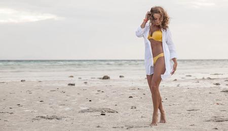 Frau im Bikini und Hemd am tropischen Strand