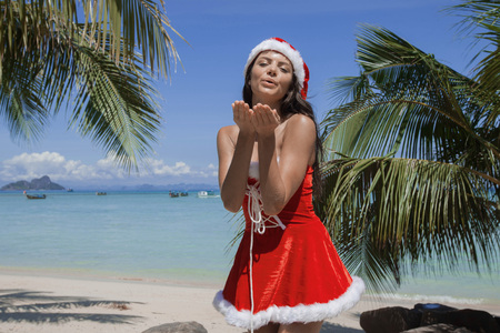 Beautiful woman in Mrs. Claus custume on tropical beach with palms, Christmas vacations concept Stock Photo