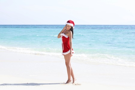 mrs: Beautiful woman in Mrs. Claus custume on tropical beach, Christmas vacations concept