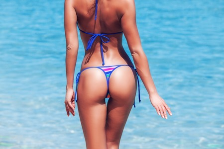 hip: Woman in bikini on blue sea background, close up photo of hips