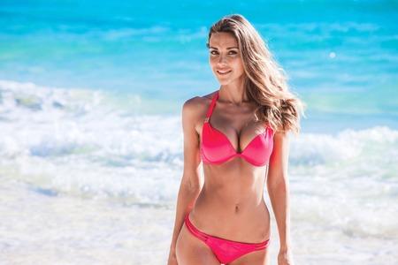Mooie jonge vrouw in sexy bikini staan op zee strand