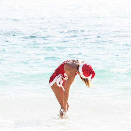 sexy costume: Beautiful woman in Mrs. Claus custume on tropical beach, Christmas vacations concept