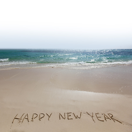Happy new year handwriting on tropical sea beach