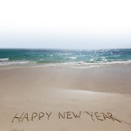 new year eve: Happy new year handwriting on tropical sea beach