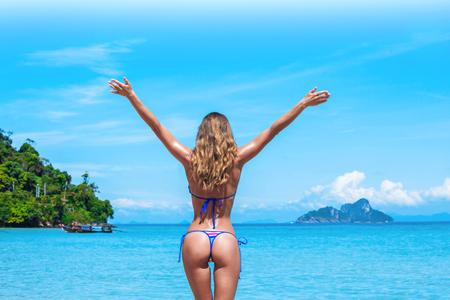 Mujer feliz con las manos levantadas en la playa en Tailandia