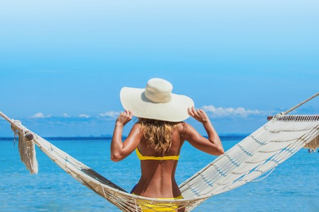 hummock: Woman in sunhat swinging in hummock on blue sea background