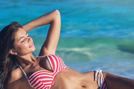 sea beach: Young woman in bikini laying by tropical sea
