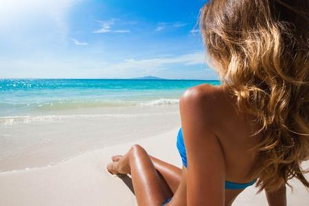 maillot de bain fille: Femme en bikini assis sur la plage journée ensoleillée