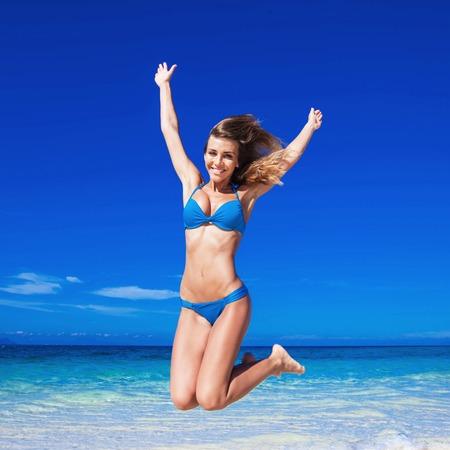 pretty young girl: Happy woman in bikini jumping on the beach